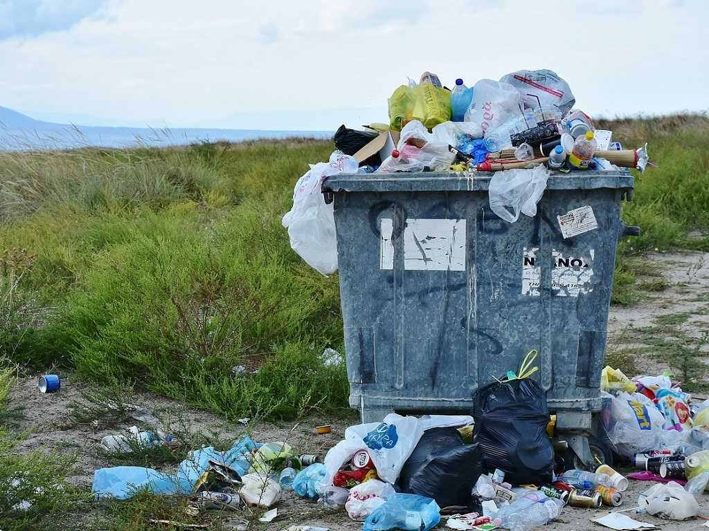 Overvolle vuilniscontainer vol wegwerp plastic en blikjes.