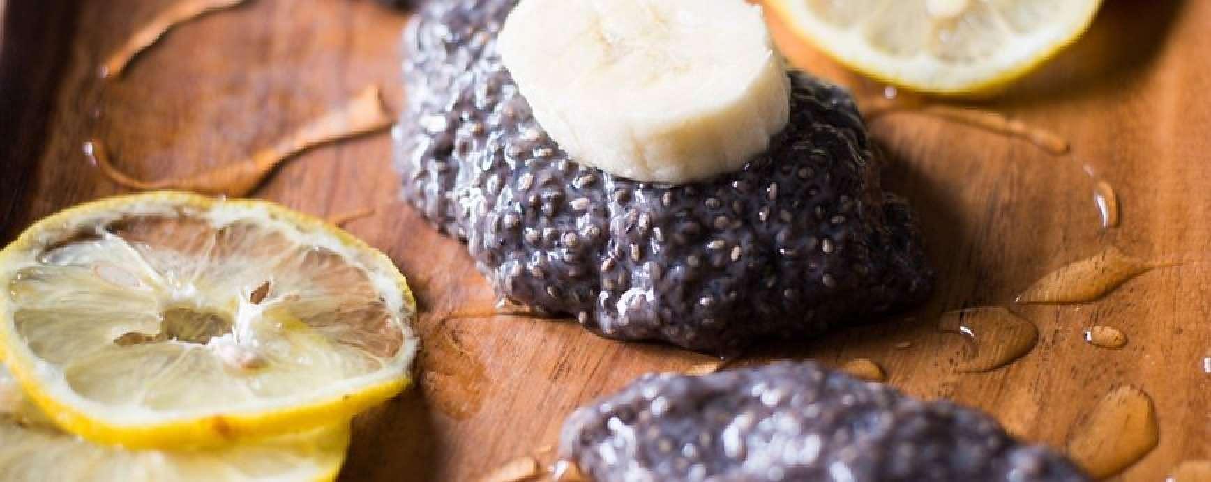 Délicieux pouding au cacao au lait d'amande végétarien avec banane et graines de chia servi sur un plateau avec des tranches de citron et des tranches de banane.