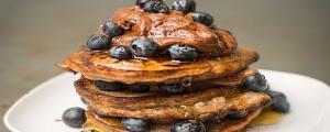 Stapel pancakes overladen met bosbessen en een topping van chocolade en kokosbloesemsuiker