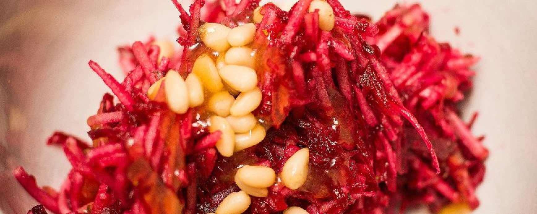 La belle salade de légumes crus pourpre servie dans un plat avec des pignons de pin supplémentaires